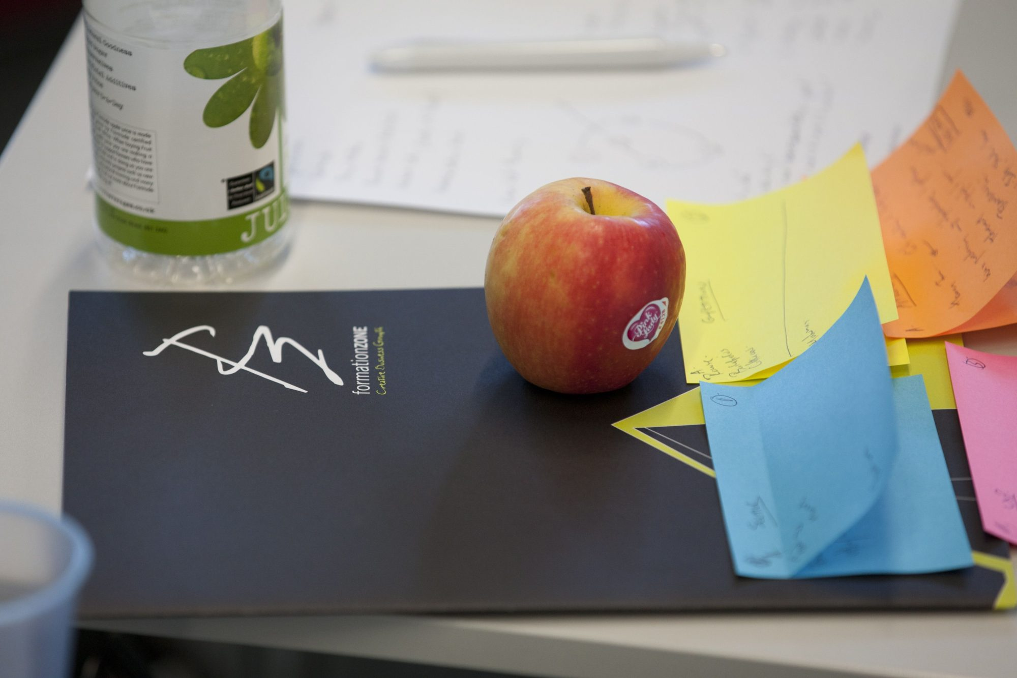 An apple on a Formation Zone folder at a Challenge workshop