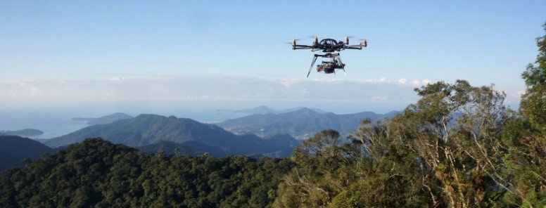 Drone flying over tree covered mountains