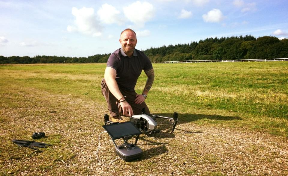 Jamie Haigh, of Shield, with a drone in a field, with trees and clear sky in the background